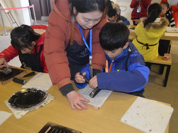 龙景书院的工作人员正在指导小记者使用活字印刷术。新华网发(李晓川 摄).JPG