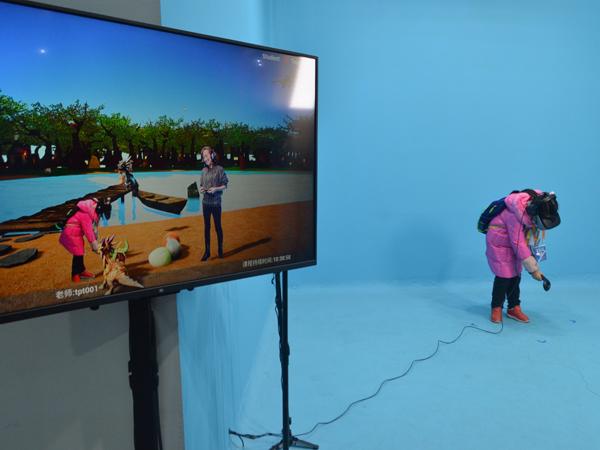 小记者沉浸在MR混合现实技术中,在外教的指示下,与小恐龙互动。新华网发(郝梦尔 摄).JPG